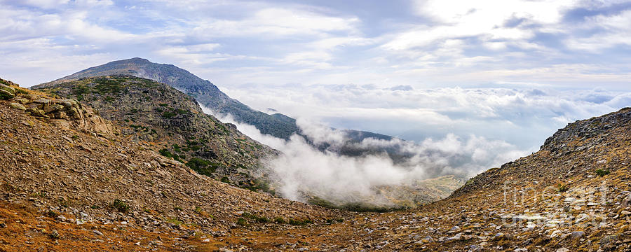 Panoramic image of the views of the Sierra de Guadarrama with its clouds from the top of a mountain peak. by Joaquin Corbalan