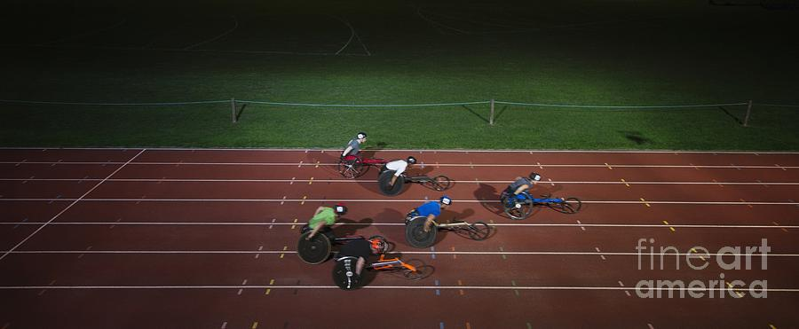 Ambition Photograph - Paraplegic Athletes Racing Along Sports Track In Night by Caia Image/science Photo Library