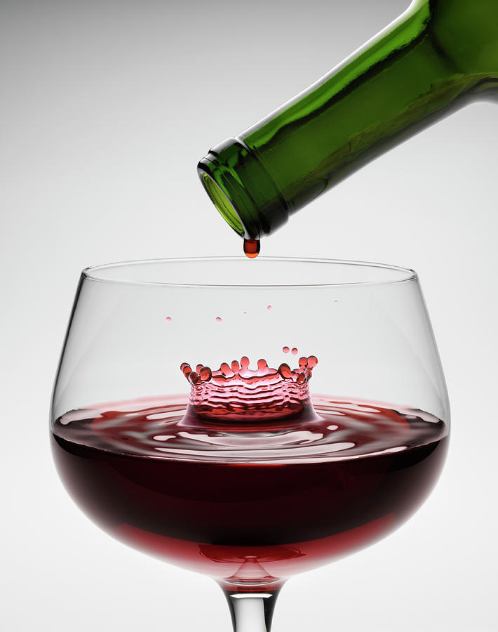 Red Wine Being Poured Into Wineglass Photograph by Don Farrall