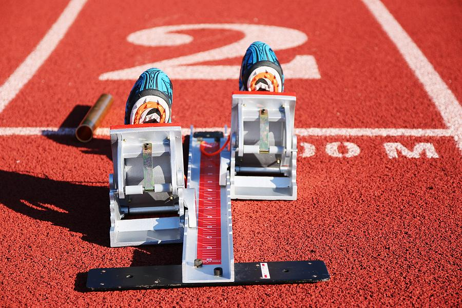 Starting Blocks Photograph - Starting Blocks With Spikes In Them And A Baton On The Track by David Wood