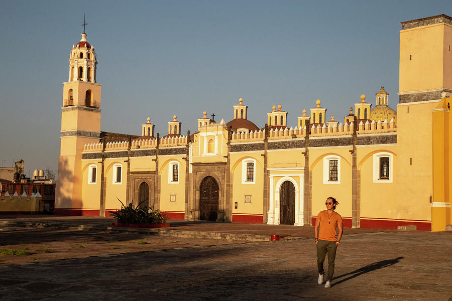 Mexico Photograph - Young Mexican Man Walking In Front Of Yellow Church In Cholula, Puebla by Cavan Images