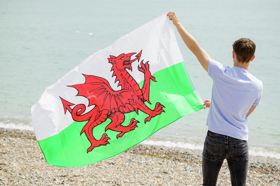 Caucasian male on a beach holding a Welsh flag by Ben Gingell