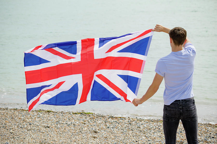 Caucasian male on a beach holding a British flag by Ben Gingell