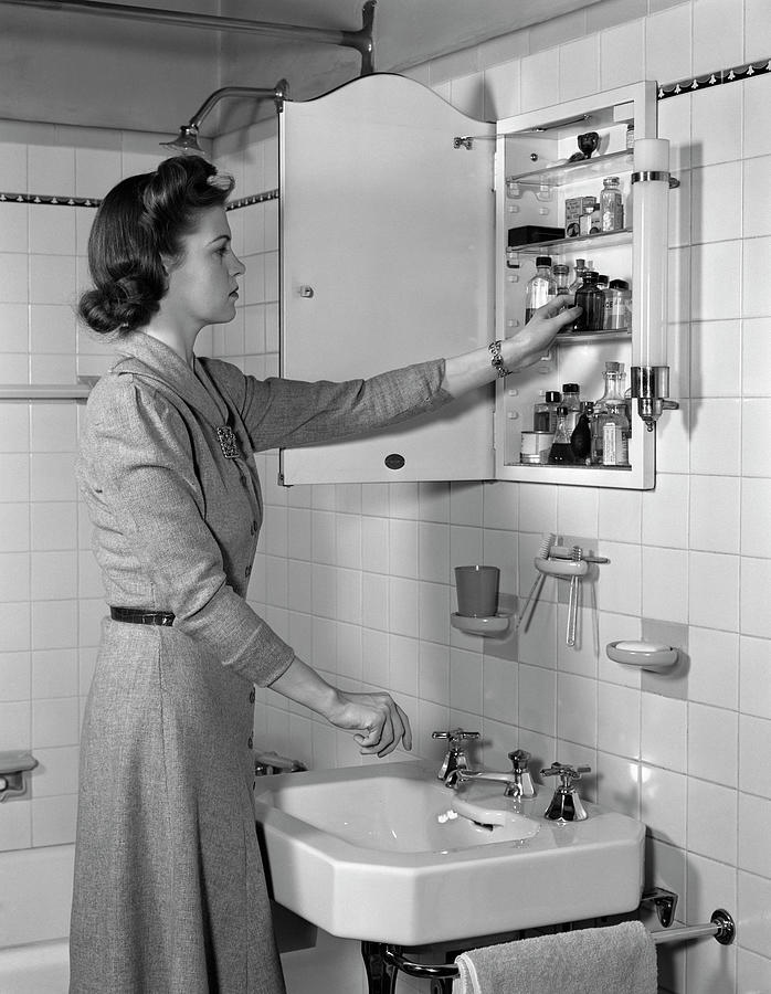 1940s Woman Reaching Into Bathroom Photograph By Vintage Images