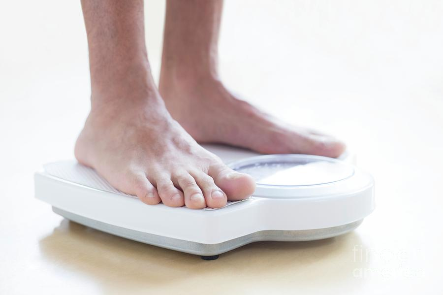 Adult Photograph - Man Standing On Weighing Scales by Science Photo Library