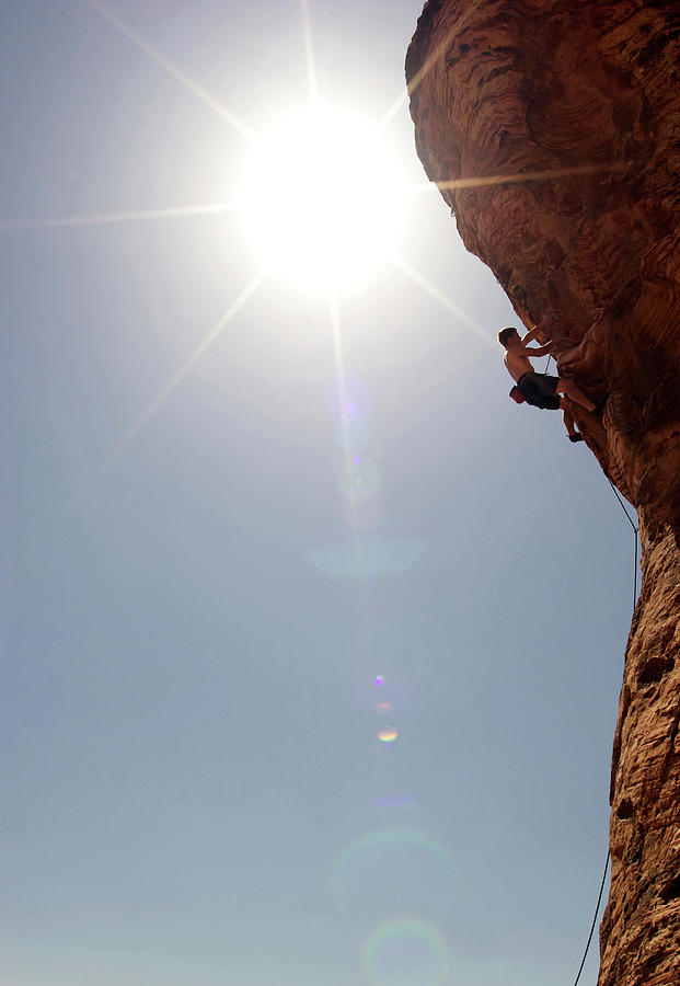 A Rock Climber Ascends A Red Rock Face Photograph by Jared Mcmillen