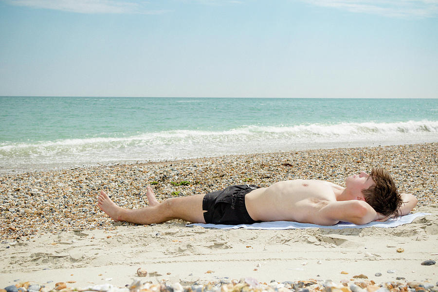 Caucasian male on a beach relaxing by Ben Gingell
