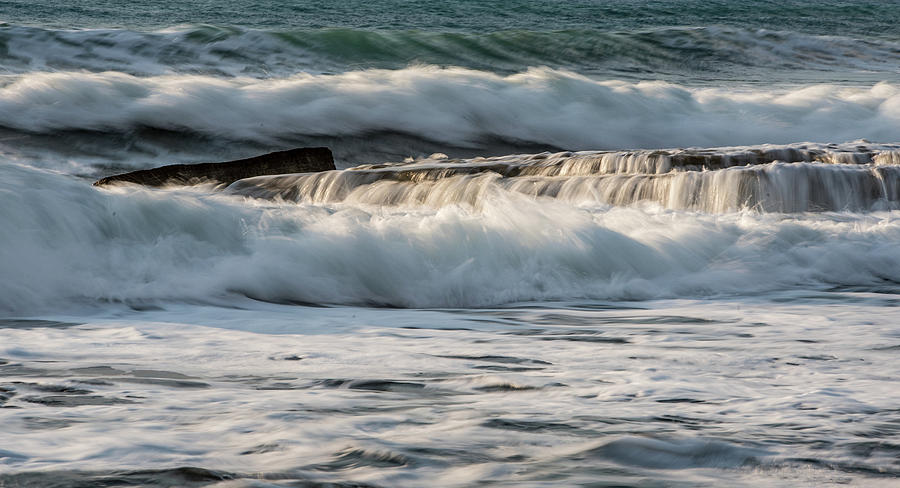 Rocky seashore with wavy ocean and waves crashing on the rocks  by Michalakis Ppalis