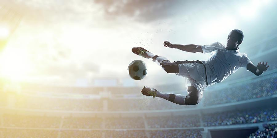 Soccer Player Kicking Ball In Stadium Photograph by Dmytro Aksonov