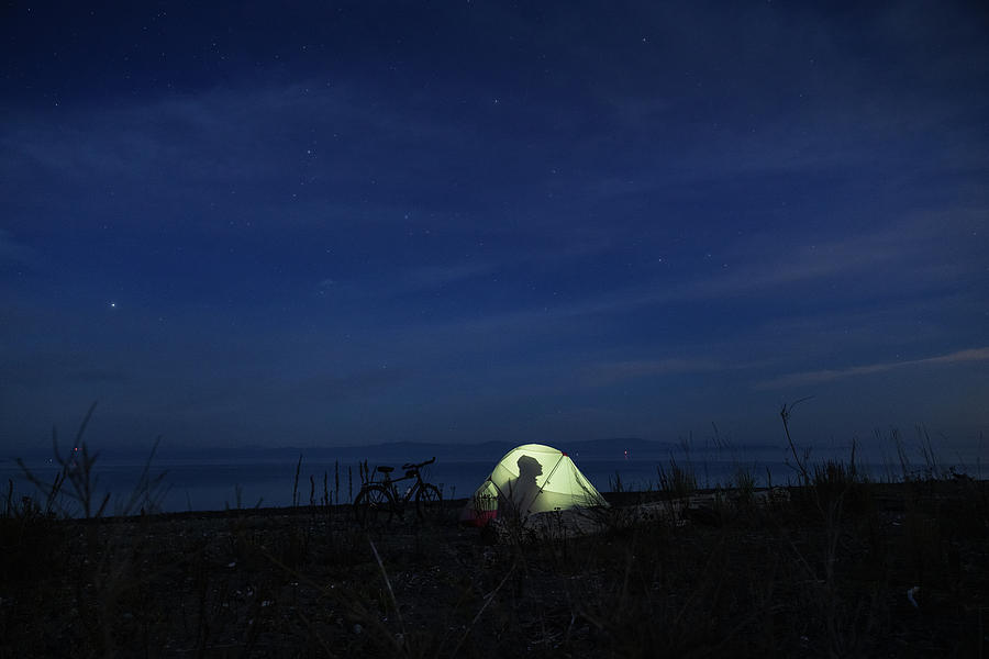 A Cyclist Camping In The Dark In Vancouver Island, Bc, Canada