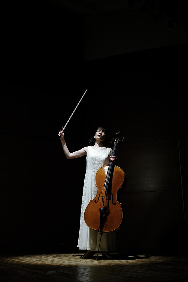 A Female Cellist Raising Bow Of Cello Photograph by Sot
