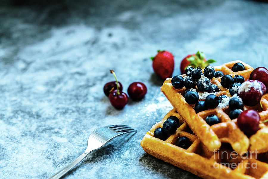 A fork on a rustic table ready for dessert, a waffle with healthy red fruits. by Joaquin Corbalan