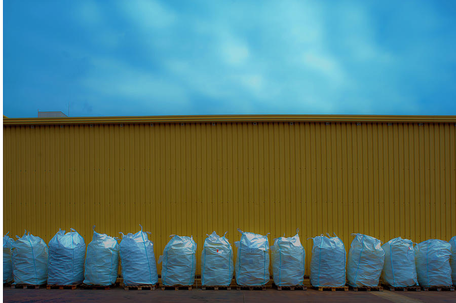 A Line Of  Sacks On Pallets Against A Photograph by Marco Vacca