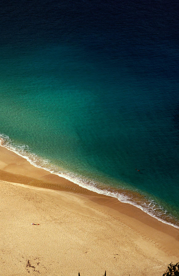 A Lone Sunbather Stretches Out On The Photograph by Ann Cecil
