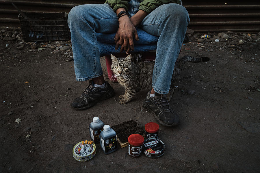 A Mexican shoe polisher with his cat near the US/Mexico border wall in Tijuana by Kamran Ali