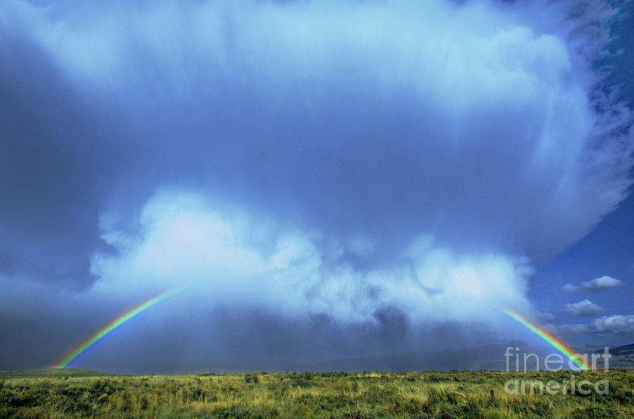 a rainbow in clouds elk refuge grand tetons np wyoming by Dave Welling