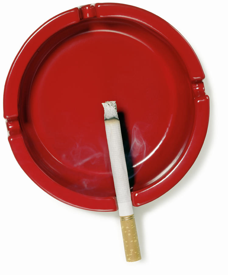 A Red Ashtray With A Burning Cigarette Photograph by Steve Wisbauer