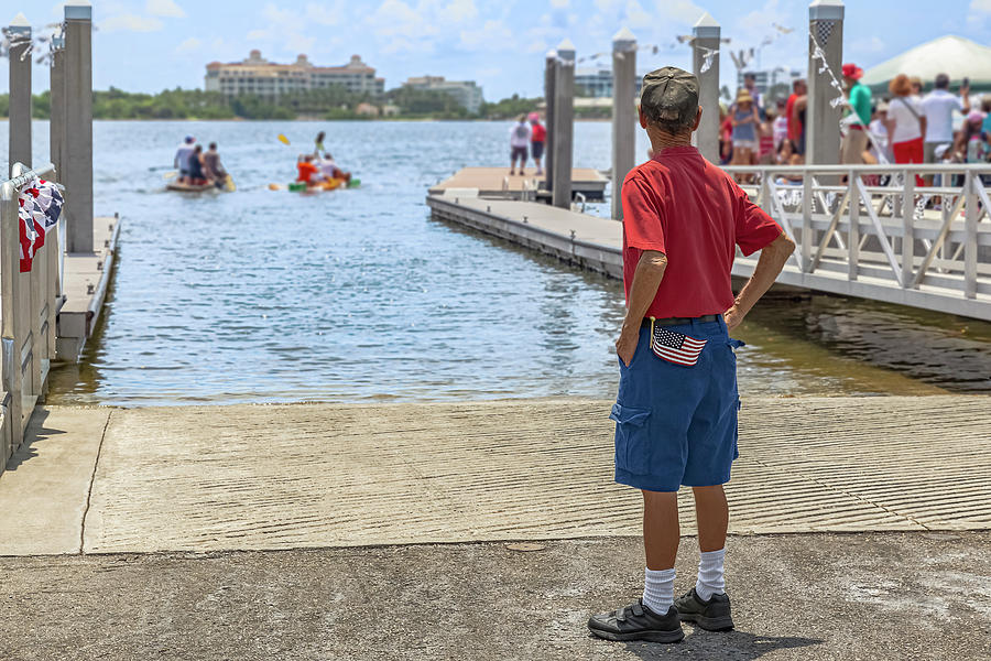 A retired veteran looks down a boat launching slip as the small  by Manny DaCunha