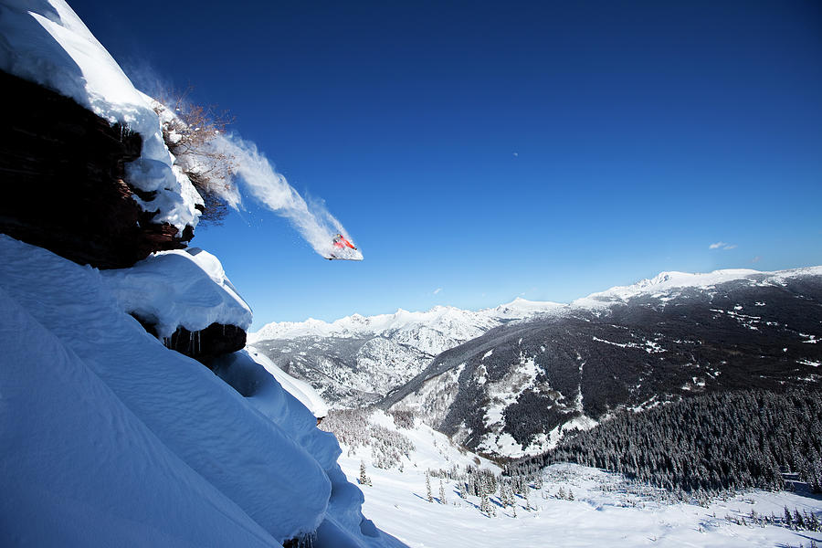 A Snowboarder Jumps Off A Cliff Into Photograph by Patrick Orton
