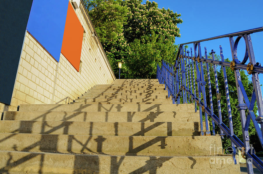 A stone staircase with abstract shadow symbols leads upwards. by Ulrich Wende