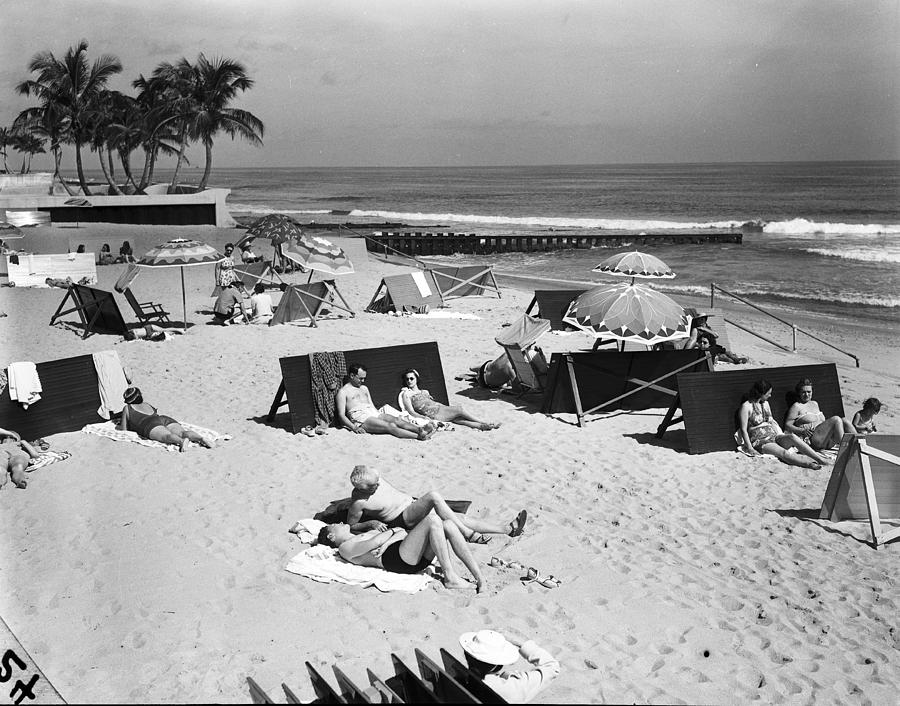 A View Of Sunbathers Lying On A Beach Photograph by Bert Morgan