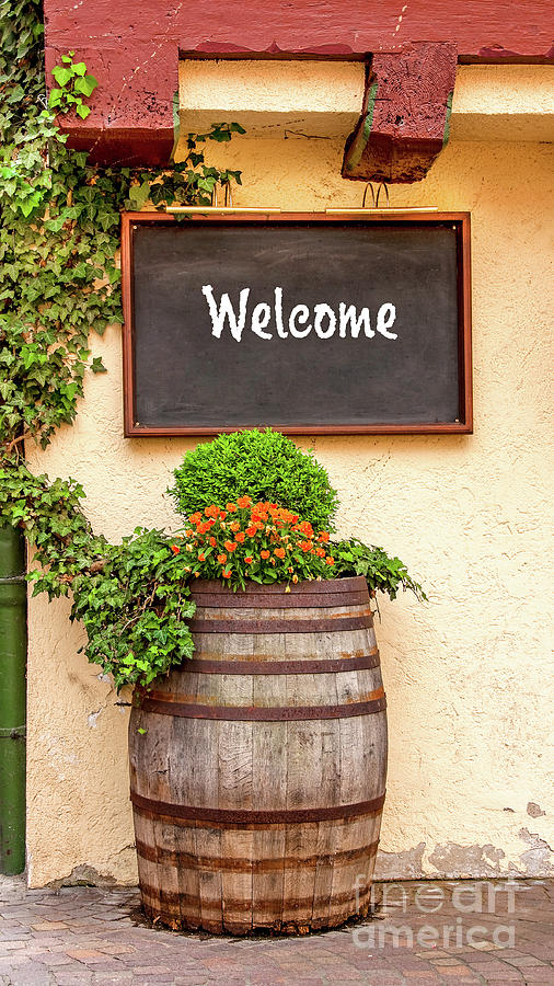 A Welcome on the menu board and a decorative wine barrel at the inviting front of a wine bar. by Ulrich Wende
