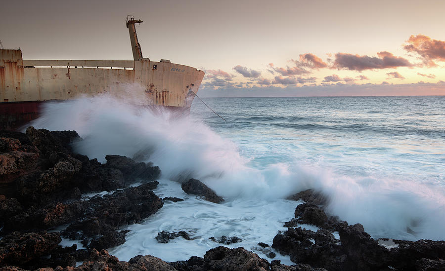 Abandoned ship in the stormy sea with big wind waves on sunset. by Michalakis Ppalis
