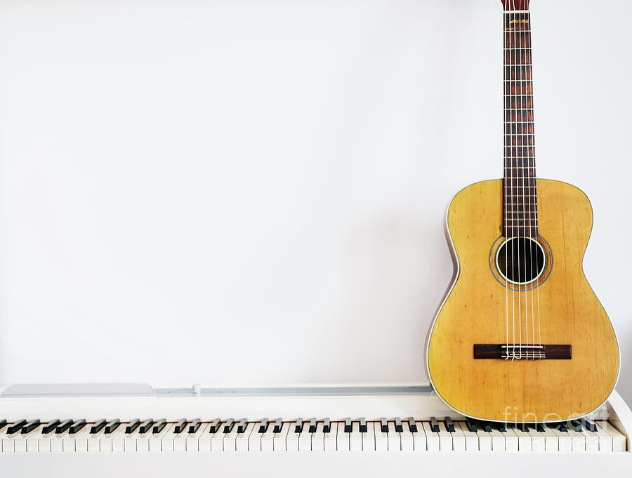 Acoustic guitar on piano keyboard in front of white wall. by Jelena Jovanovic