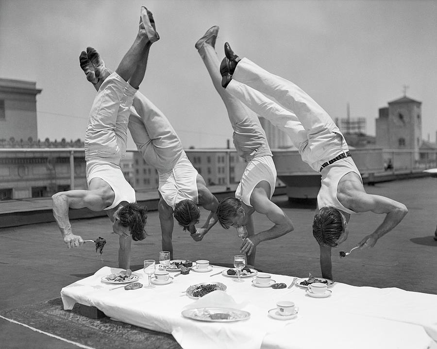 Acrobats Eat While Doing Handstands Photograph by Bettmann