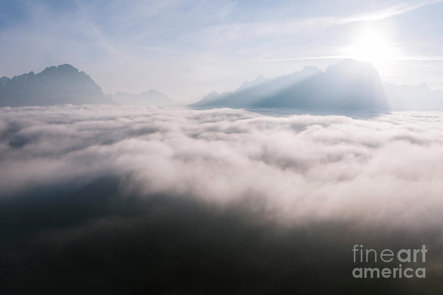 Above Photograph - Aerial View Of Low Clouds And Mountain Peak At Sunrise by Matteo Colombo