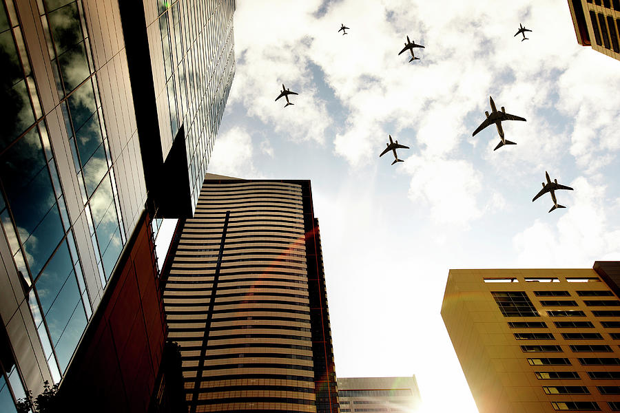 Airplanes Flying Over Buildings Photograph by Thomas Northcut