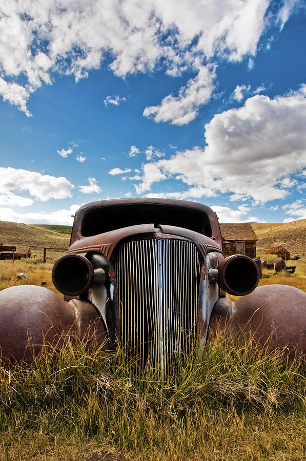 An Old Abandoned Car Rusts Away In The Photograph by Rachid Dahnoun