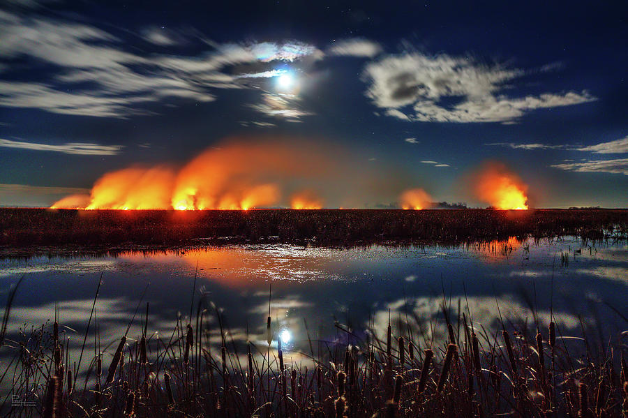 As the World Burns-  Cattails being burned off in moonlight at Devils Lake ND by Peter Herman