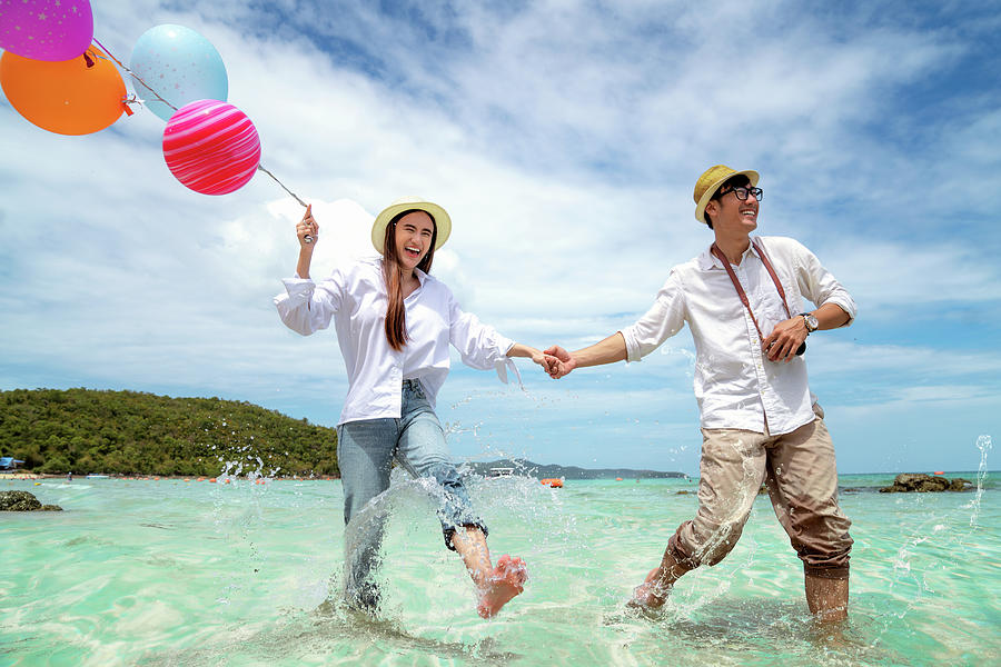 Asian couple run and happy on Pattaya beach with balloon on hand by Anek Suwannaphoom