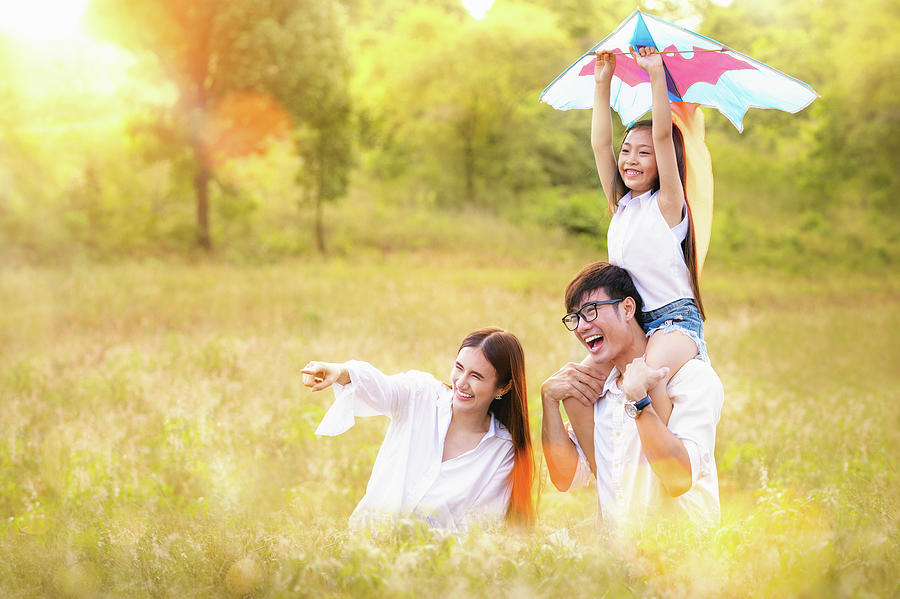 Asian family father, mother and daughter play ta kite in the out by Anek Suwannaphoom