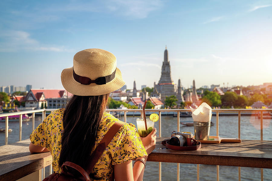 Asian girl sitting and relax in wat with Wat Arun temple backgro by Anek Suwannaphoom
