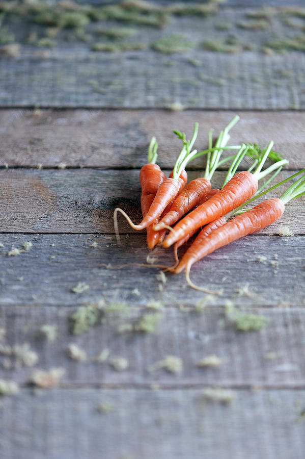 Baby Carrots On Rustic Table Photograph by Devin Hart