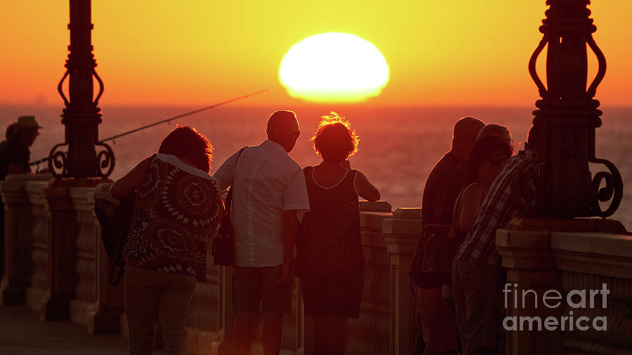Back lighted Couple Staring at the Sunset by Pablo Avanzini