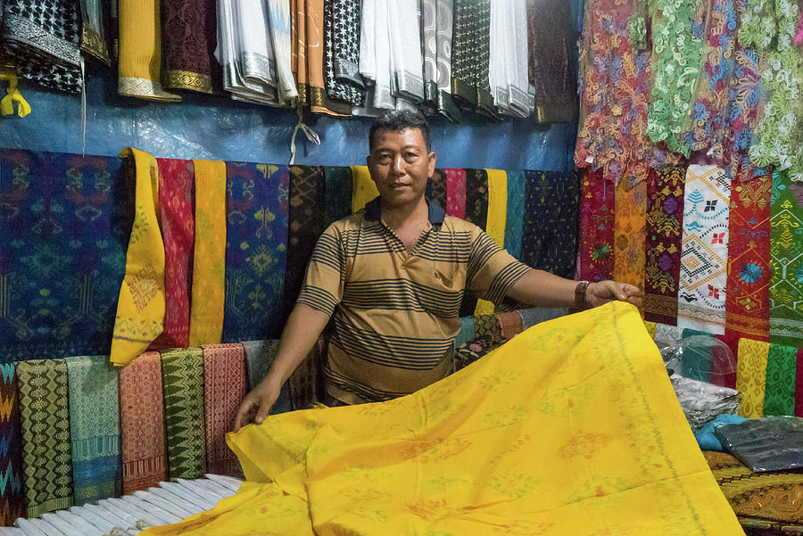 Bali Fabric Vendor at Night by Harry Donenfeld