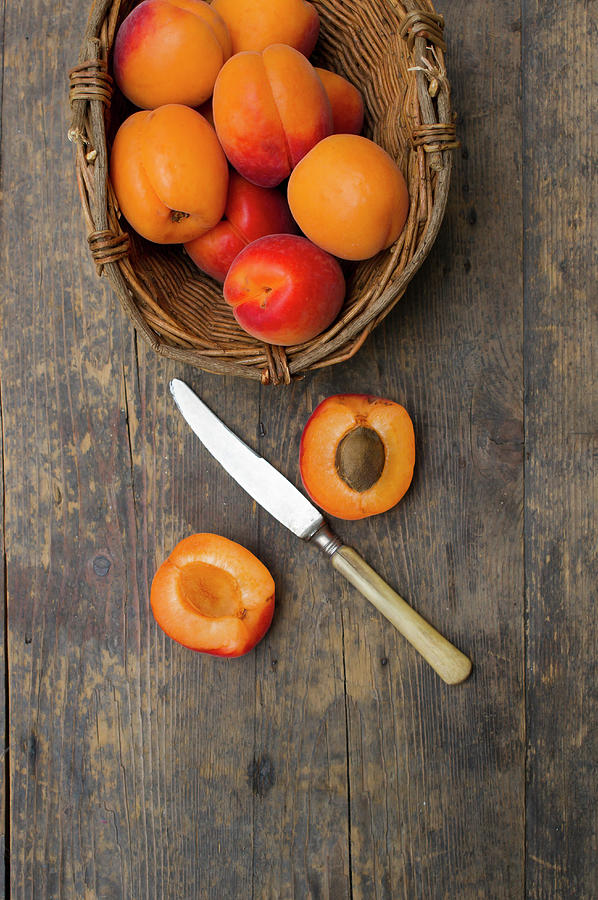 Basket Of Apricots With Knife On Wooden Photograph by Westend61