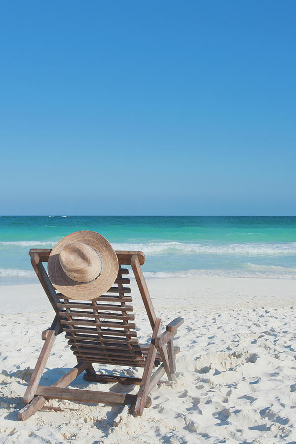 Beach Chair With A Hat On An Empty Beach Photograph by Sasha Weleber