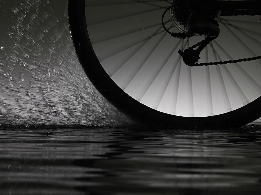 Bike Riding  Through Water Photograph by Jonathan Knowles