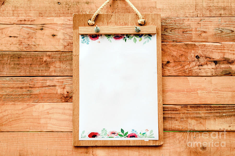 Blank paper on a clipboard to take notice to announce news on a romantic vintage style wooden board. by Joaquin Corbalan