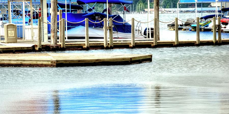 Blue awning reflected in smooth, calm water. by Jerry Sodorff