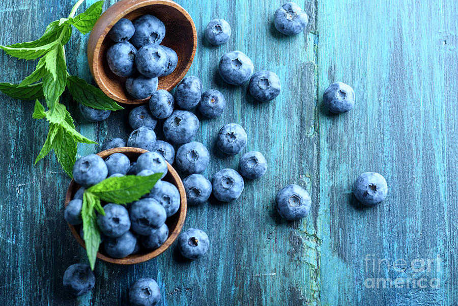 Bowl Of Fresh Blueberries On Blue Rustic Wooden Table From Above by Jelena  Jovanovic
