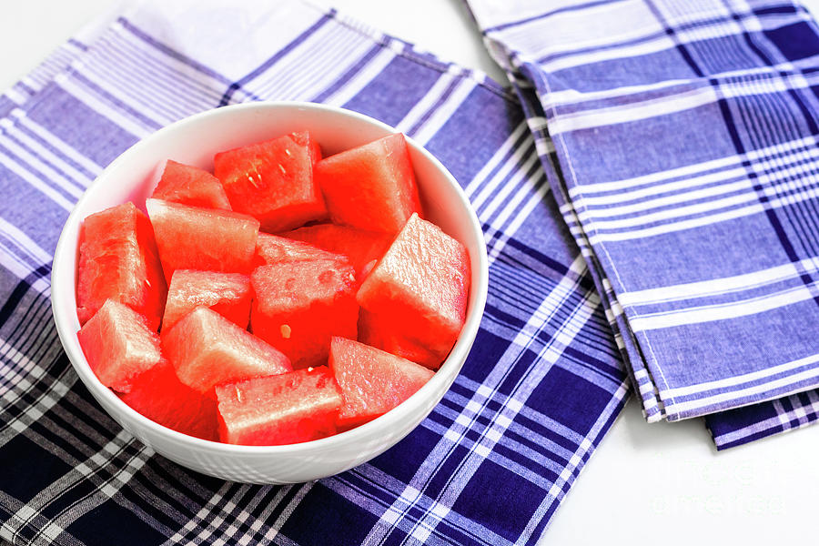 Bowl with pieces of red watermelon on a blue napkins on white ba by Joaquin Corbalan