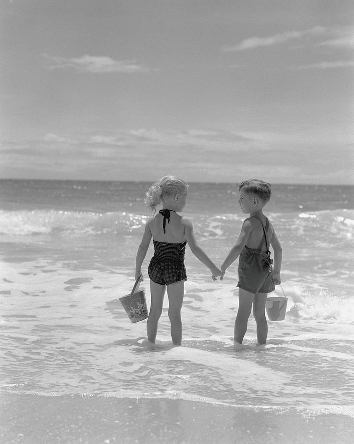 Boy And Girl Standing On Beach, Holding Photograph by H. Armstrong Roberts