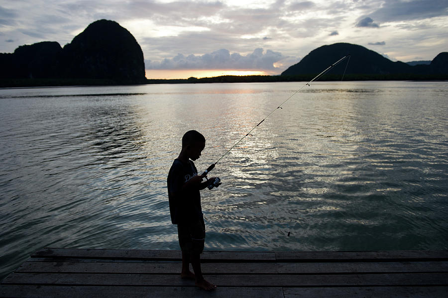 Boy Fishing On Pier Photograph by Kampee Patisena
