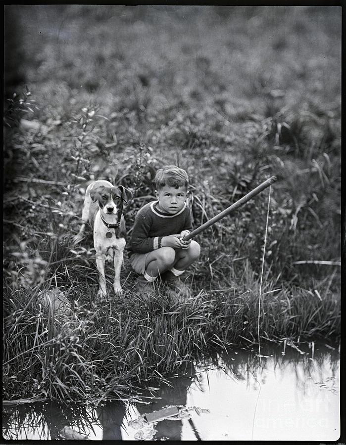 Boy With Dog Fishing Photograph by Bettmann