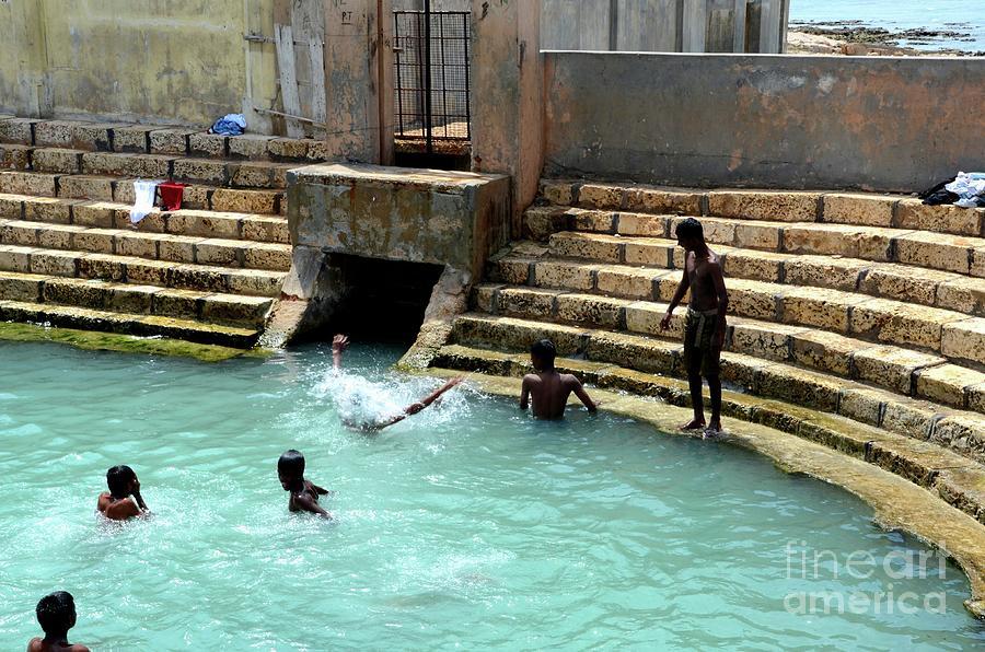 Boys play and bathe in Keerimalai fresh water spring tank by ocean water Jaffna Sri Lanka by Imran Ahmed